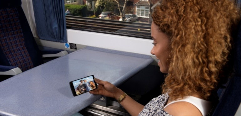 Woman using Sky Mobile on the train