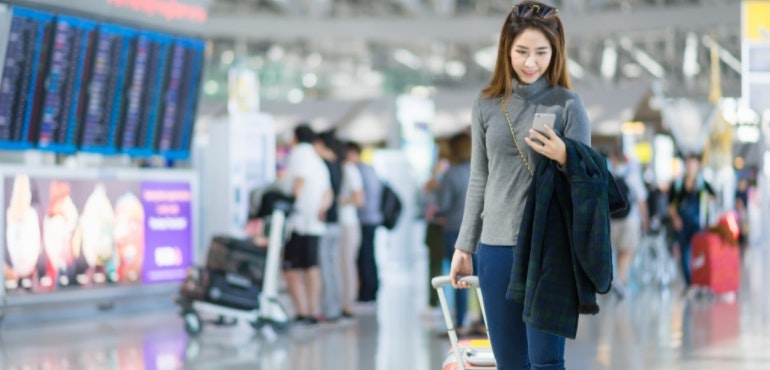 International roaming woman using phone at airport
