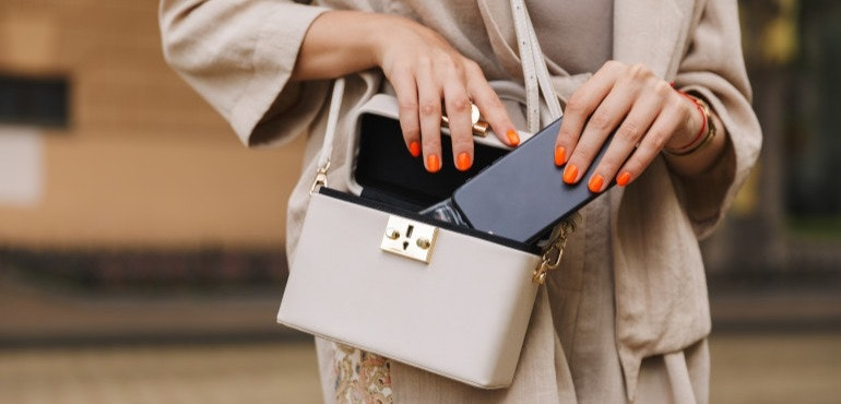 Woman putting smartphone in her bag