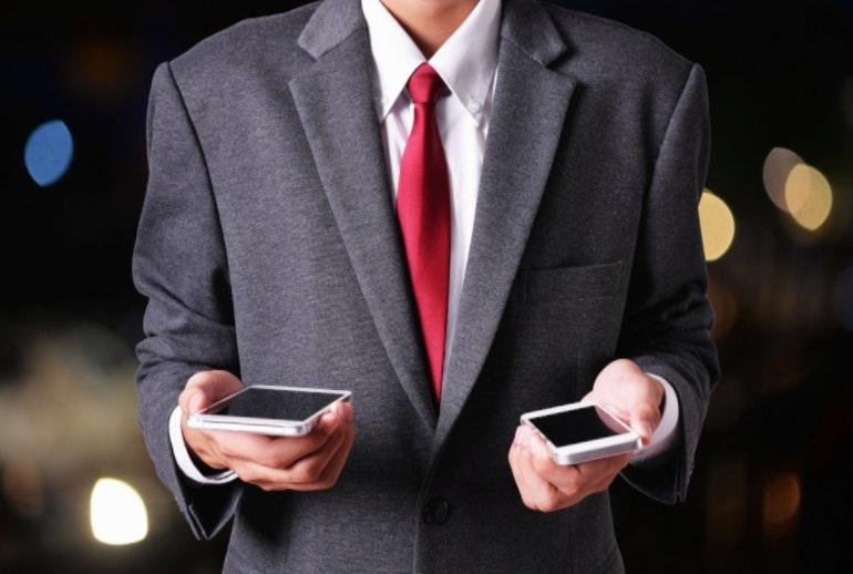 Мужчина держит два телефона передачи данных
